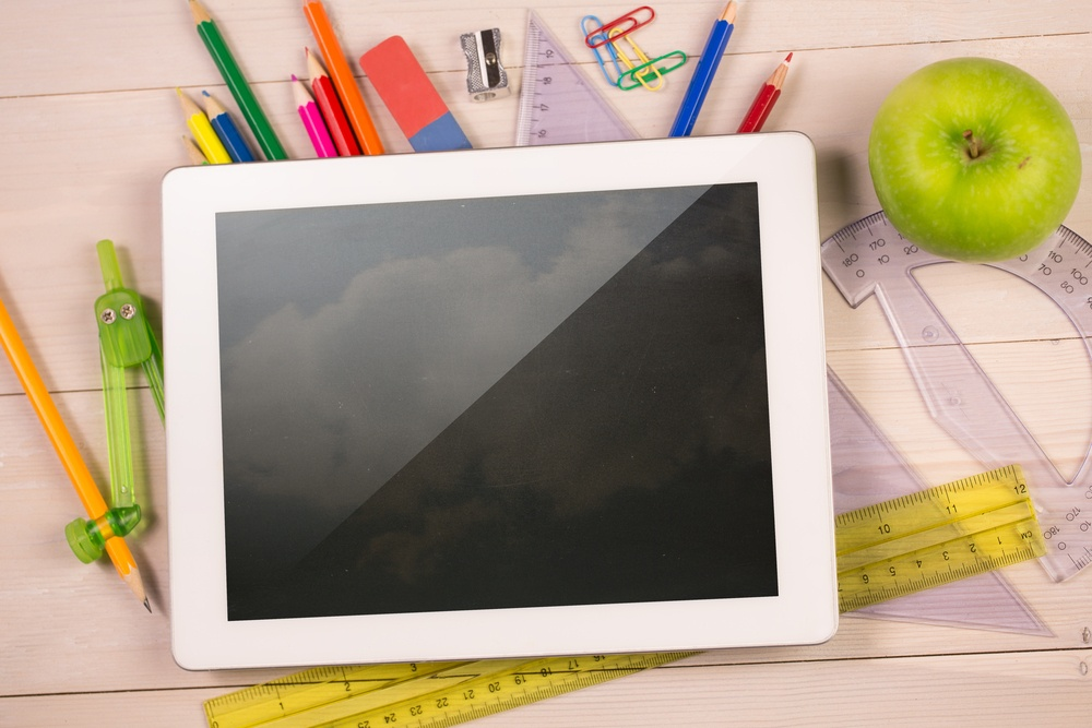 Composite image of digital tablet on students desk showing clouds