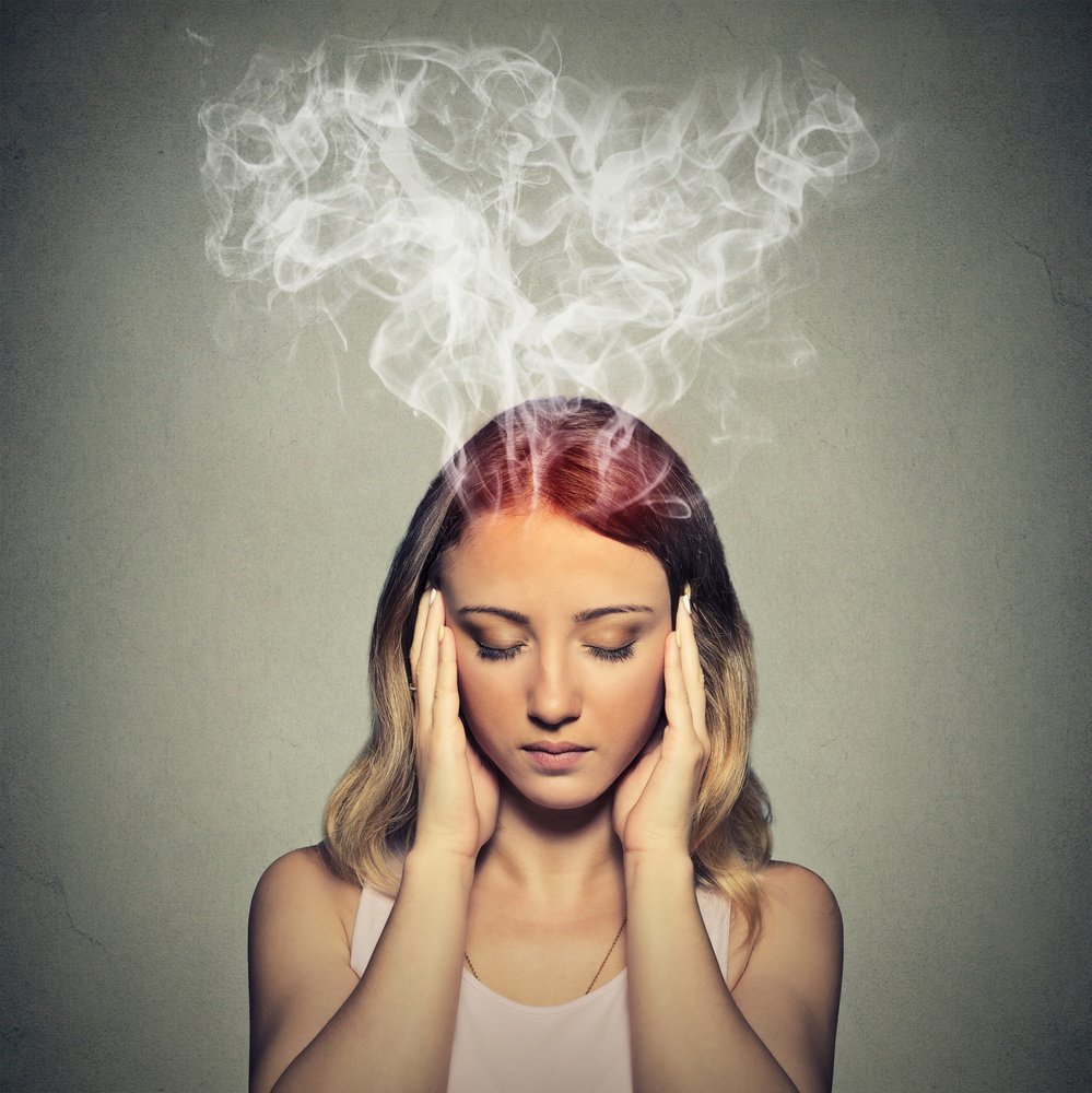 Portrait young stressed woman thinking too hard steam coming out up of head isolated on grey wall background. Face expression emotion perception.jpeg