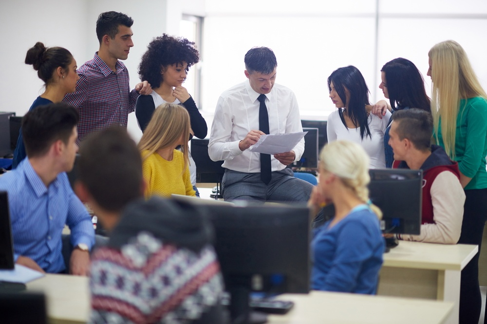 group of students with teacher in computer lab classrom learrning lessons,  get help and support.jpeg