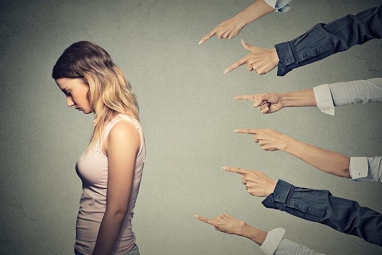 Concept of accusation guilty person girl. Side profile sad upset woman looking down many fingers pointing at her back isolated on grey office wall background. Human face expression emotion feeling.jpeg