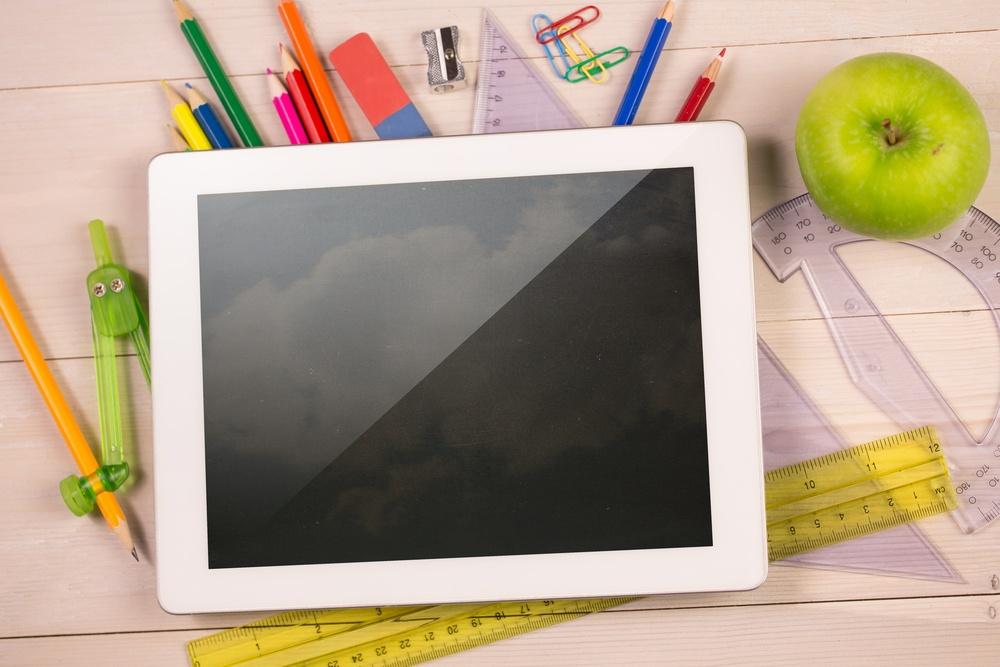 Composite image of digital tablet on students desk showing clouds