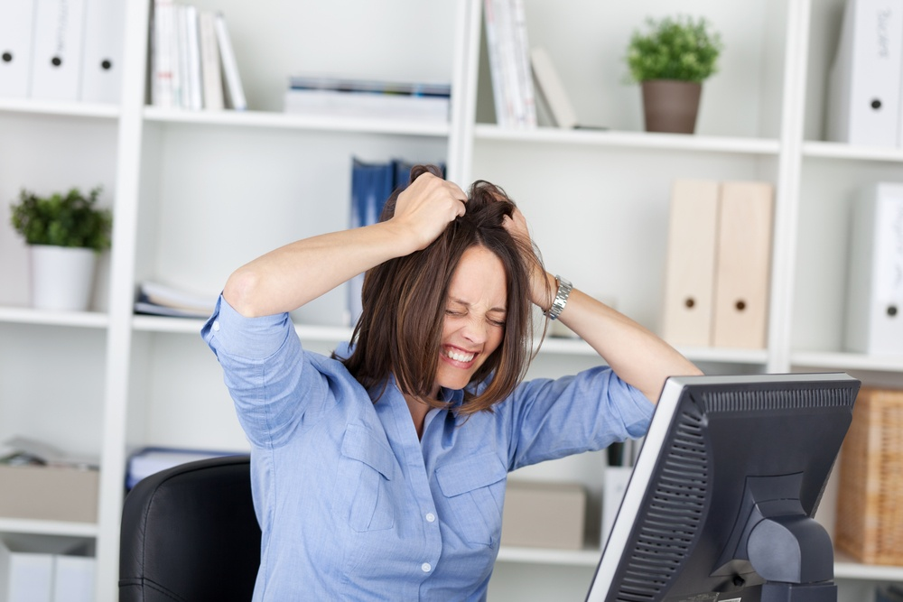 Irritated businesswoman pulling her hair while sitting in office.jpeg
